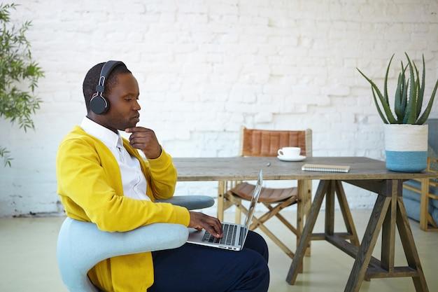 노란색 카디건과 일반 노트북에서 wifi를 사용하여 온라인으로 공부하는 무선 헤드셋을 착용 한 집중된 아프리카 학생. 휴대용 컴퓨터에서 원격으로 작업하는 진지하고 어두운 피부의 프리랜서