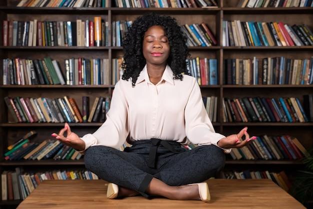 곱슬머리를 한 집중된 아프리카계 미국인 여성 사업가는 사무실 책장에 있는 갈색 나무 탁자 위에 요가 포즈를 취하고 있는 명상을 하고 있다
