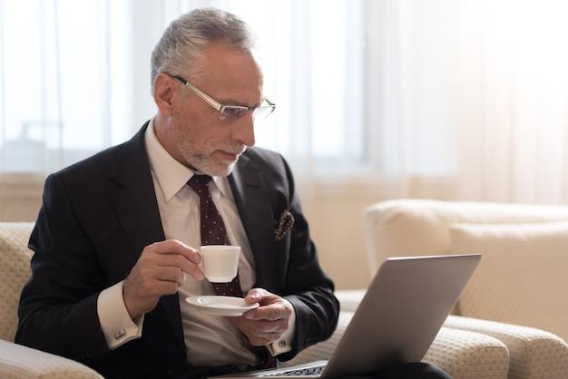 一杯のコーヒーを保持し、ラップトップを見て、眼鏡をかけている間ホテルに座っている集中した年配のひげを生やしたビジネスマン