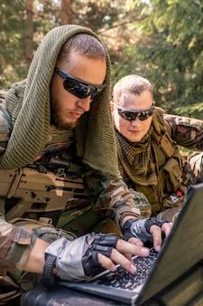 군용 컴퓨터를 사용하여 선글라스를 끼고 숲속의 군사 기지와 연락하는 동안 집중된 육군 프로그래머