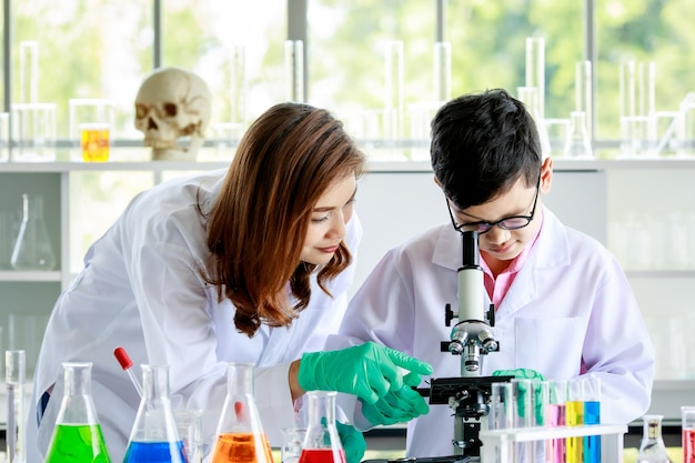 Concentrated asian boy examining liquids through microscope while conducting experiment in school laboratory with female teacher.