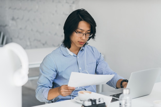 Концентрированный азиатский офисный работник в наушниках, читая документы на рабочем месте. внутренний портрет китайского внештатного ит-специалиста пьет кофе за ноутбуком.