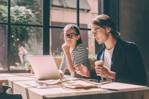 직장에서 집중. 창의적인 사무실이나 카페의 나무 책상에 앉아 있는 동안 노트북을 보고 있는 자신감 있는 젊은 남성과 여성