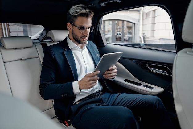 직장에서 집중. 차에 앉아있는 동안 디지털 태블릿을 사용하여 작업하는 전체 정장에 자신감이 젊은 남자