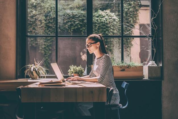 직장에서 집중. 스마트 캐주얼 차림의 자신감 있는 젊은 여성은 창의적인 사무실이나 카페의 창가에 앉아 노트북 작업을 하고 있습니다.