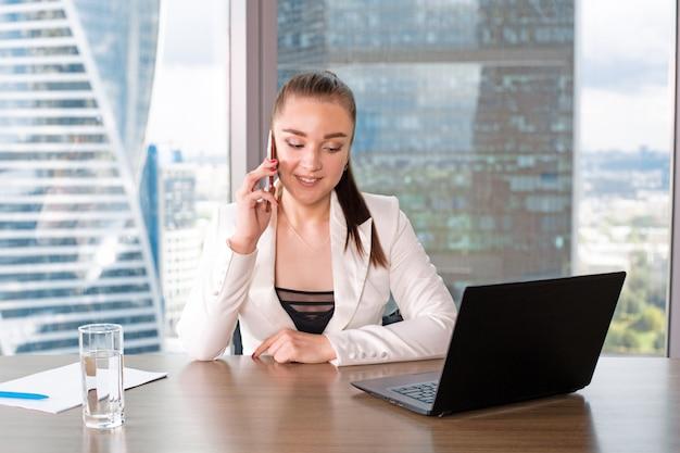 직장에 집중했다. 창조적 인 사무실에서 창 근처에 앉아있는 동안 스마트 캐주얼에 자신감이 젊은 여자가 노트북에서 작동