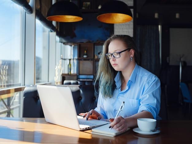Сосредоточен на работе. уверенная молодая женщина больших размеров в элегантной повседневной одежде работает на ноутбуке, сидя у окна в креативном кафе