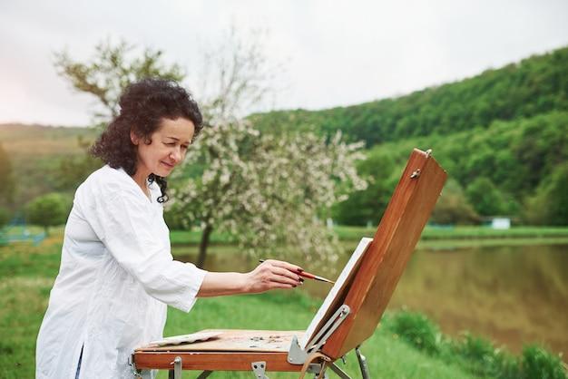仕事に集中。屋外の公園で黒い巻き毛を持つ成熟した画家の肖像