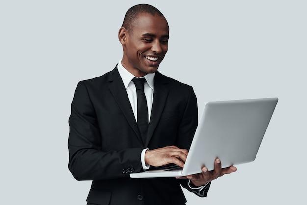 직장에서 집중. 회색 배경에 서 있는 동안 컴퓨터를 사용하여 작업하는 formalwear에서 젊은 아프리카 남자