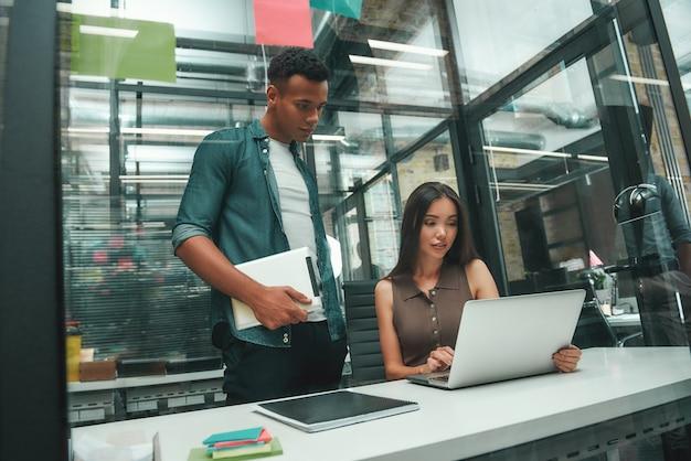 Сосредоточенный на работе молодая азиатская женщина и афро-американский мужчина в повседневной одежде, глядя на