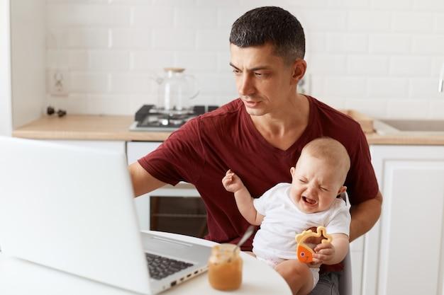 カジュアルなスタイルの栗色のtシャツを着て、ラップトップで作業し、白いキッチンに座って彼の小さな赤ん坊の娘の世話をしている、集中した魅力的なブルネットの男性フリーランサー。