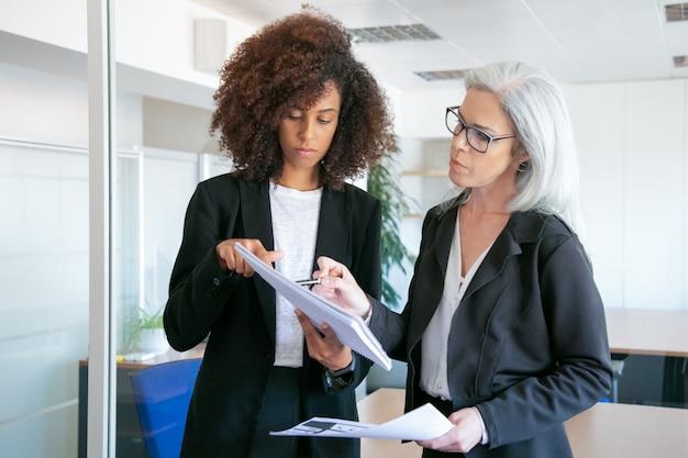 Концентрированные привлекательные бизнес-леди, сравнивающие данные аналитики. успешные уверенные в себе женщины-профессионалы, читающие документы или отчеты в конференц-зале. работа в команде, бизнес и концепция управления