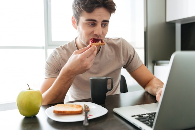 Concentrated attractive man using laptop while eating breakfast