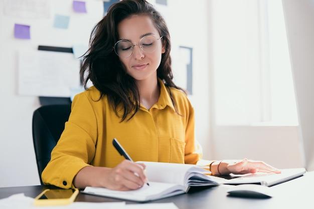 사무실 책상에 siting 및 그녀의 노트북에 계획을 작성하는 매력적인 여자를 집중