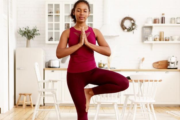 집중된 매력적인 젊은 어두운 피부 여성 레깅스를 입고 균형을 개발하기 위해 요가 아사나를하고, 나무 자세로 집에 서서, 그녀 앞에서 손을 유지하고, 나마스테를 보여주는