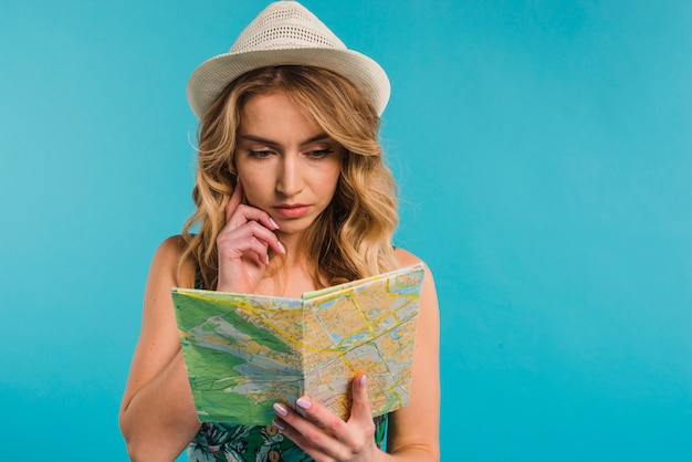Concentrated attractive young woman in hat looking at map