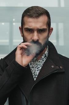Концентрированный бородатый бизнесмен курит сигарету и серьезно