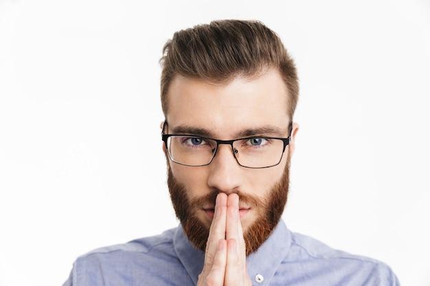 Сосредоточенный бородатый элегантный мужчина в очках смотрит