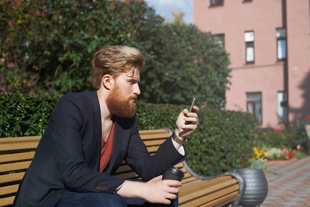 Concentrated bearded hipster using smarphone while sits on a bench