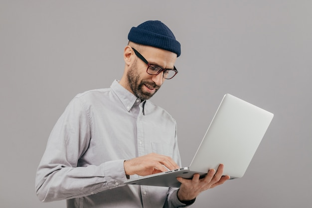Concentrated bearded male administrative worker coordinates work on distance