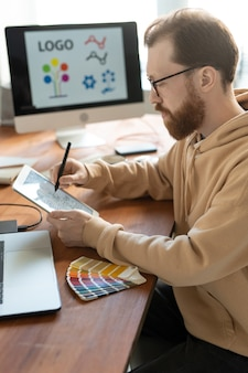 Concentrated bearded man in hoodie sitting at wooden table and using tablet while working on brand design