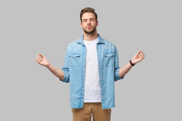Сосредоточенный бородатый мужчина медитирует и расслабляется, пытаясь успокоиться