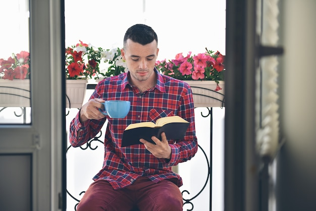 Concentrated bearded man reading books and drinking coffee