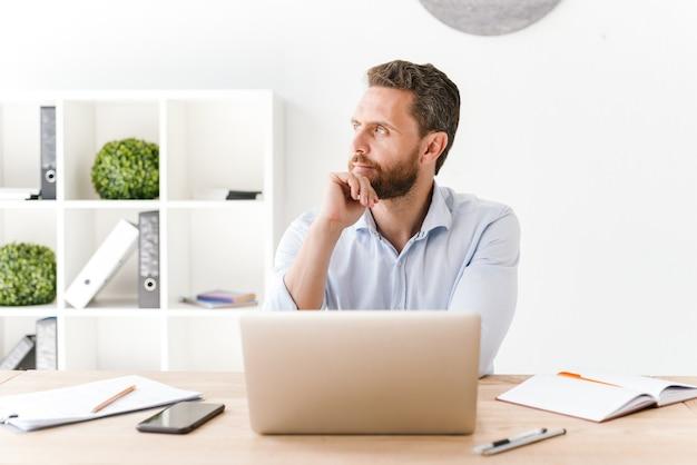 Сосредоточенный бородатый мужчина сидит в офисе