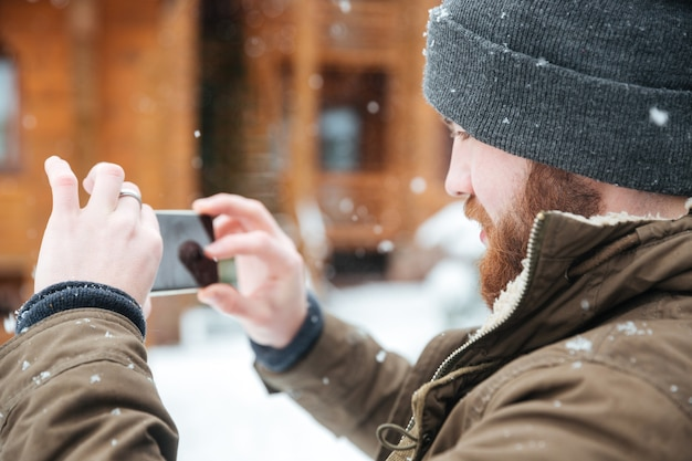 Concentrated bearded man taking pictures with cell phone in snowy weather in winter
