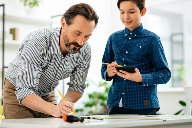テーブルの上に絵を描く集中したひげを生やした中年の男性と彼の笑顔の息子は彼の手で現代のタブレットを持って近くに立っています