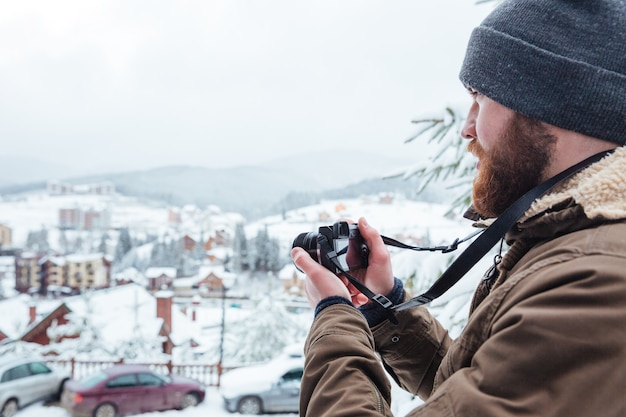 Concentrated bearded young man taking pictures of view outdoors in winter