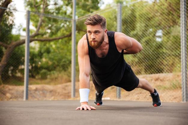 Сосредоточенный бородатый молодой спортсмен делает отжимания одной рукой на открытом воздухе