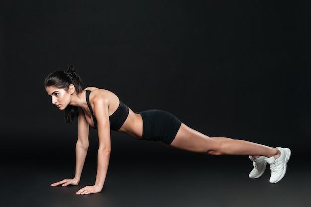 Концентрированная красивая фитнес-девушка в спортивной одежде делает доску над черной стеной