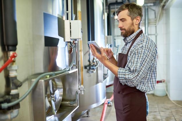 機器を調べながらタブレットを使用してビールエンジニアを集中