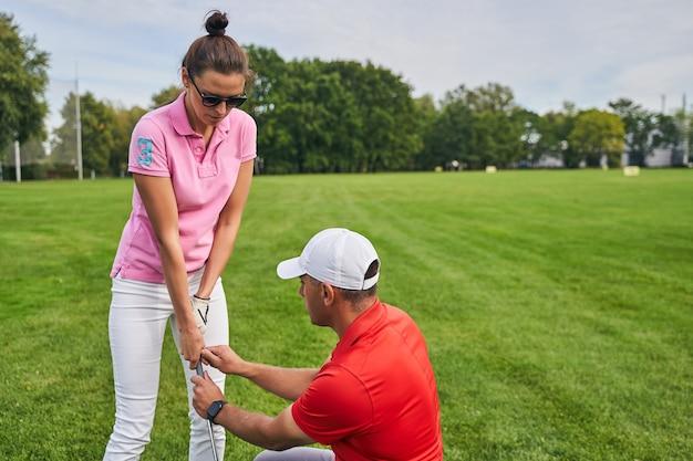 숙련 된 튜터의 도움을 받아 골프채 잡는 법을 배우는 집중 초보 골퍼
