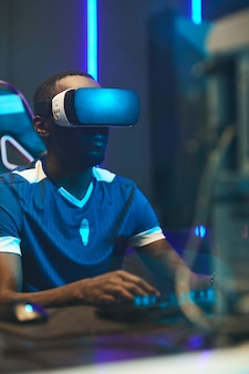 Concentrated black gamer in vr headset