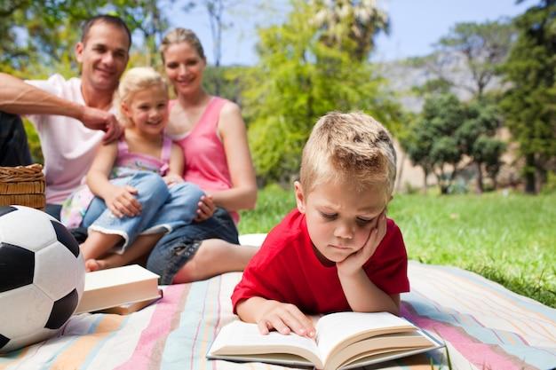 家族と一緒にピクニックをしながら集中的にブロンドの少年読書