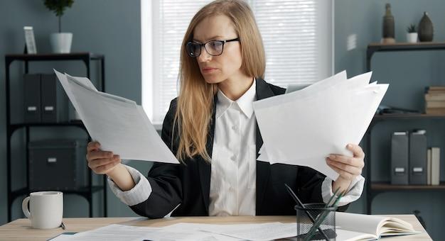 書類、紙のレポートの山を保持しているオフィスの机に座っている集中金髪のビジネスウーマン