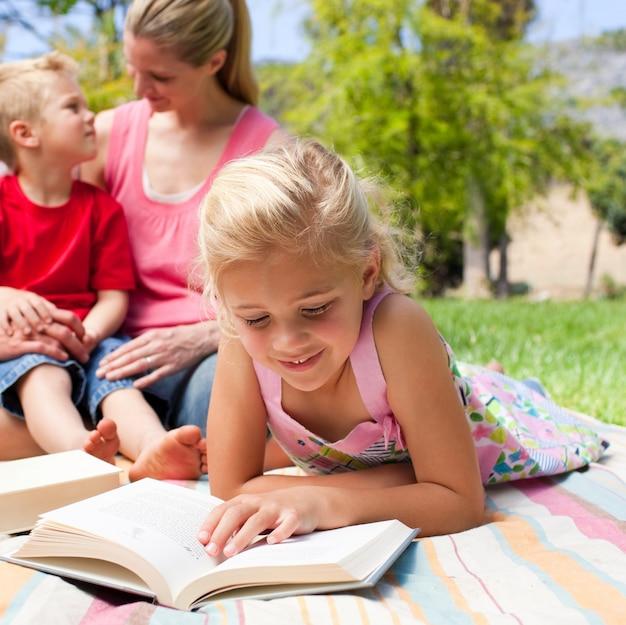 彼女の家族と一緒にピクニックをしている間に読書を集中した金髪の女の子