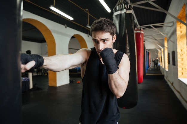 Concentrated boxer doing training with punchbag