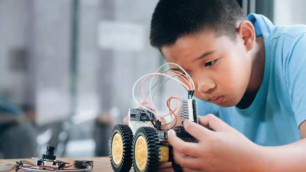 ラボでロボットを作成する集中少年。