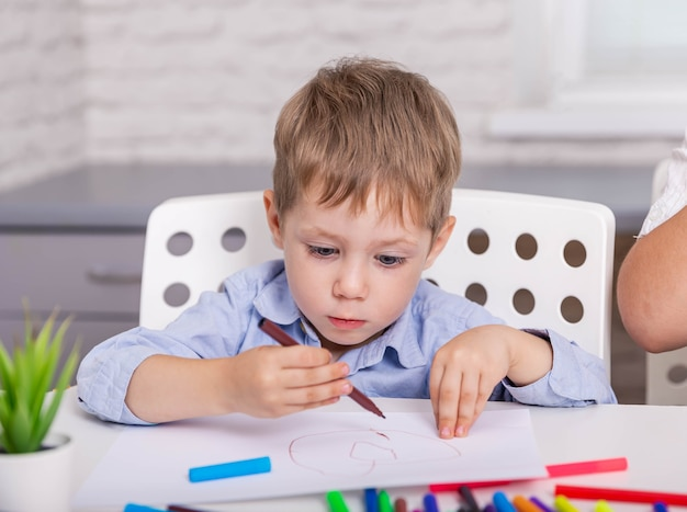 Концентрированный мальчик рисует картину с фломастером дома