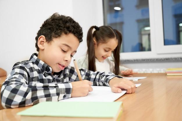 テーブルに座ってコピーブックに書いて集中している少年