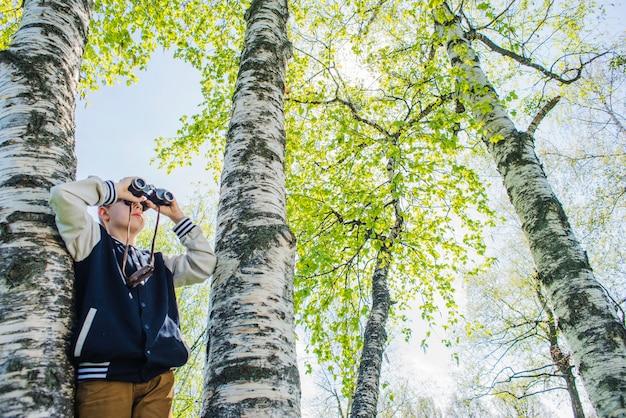 Концентрированный мальчик с биноклем в парке
