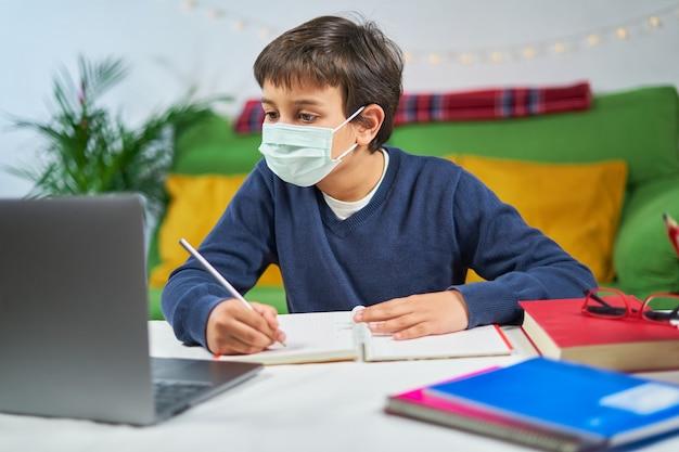 Сосредоточенный мальчик с маской для лица печатает на ноутбуке, домашний интерьер, свободное место