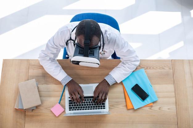 Сосредоточенная брюнетка, держащая руки на клавиатуре, проводит технические исследования