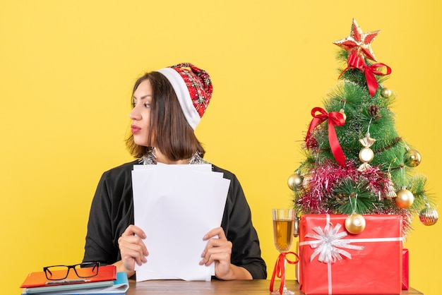 Concentrated business lady in suit with santa claus hat and new year decorations holding documents and sitting at a table with a xsmas tree on it in the office