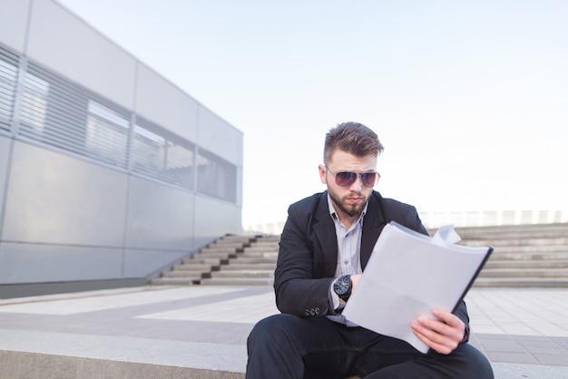 Сконцентрированный бизнесмен сидя на лестнице и смотря бумаги в его руках.