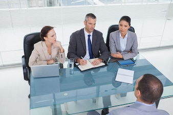 Concentrated business team interviewing experienced man