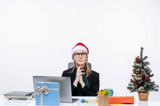 Donna d'affari concentrato con cappello di babbo natale seduto a un tavolo con un albero di natale e un regalo su di esso in ufficio su sfondo bianco